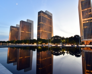 the empire state plaza agency buildings at night and a view of the reflecting pools in the evening