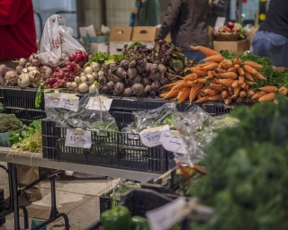 the indoor farmers market on the empire state plaza concourse featuring beets, carrots, onions, and more vegetables