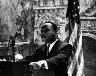 Dr. Martin Luther King, Jr. standing at a podium about to deliver a speech.