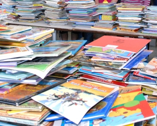 Stacks of children's books waiting to be sorted and donated to schools.