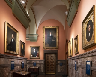 View of the Hall of Governors with portraits hanging on both sides of the wall.