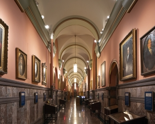 A long view of the Hall of Governors with portraits hung on both sides of the corridor.