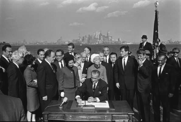 Lyndon B. Johnson signs the Immigration Act.
